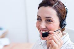 Brune souriant utilisant l'écouteur Images libres de droits
