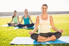 Brune sportive de sourire faisant le yoga avec ses amis Photographie stock libre de droits