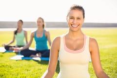 Brune sportive de sourire faisant le yoga avec ses amis Images libres de droits