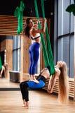 Brune sportive et la blonde de deux la jeune filles font la forme physique sur la soie a?rienne verte dans le gymnase moderne photos libres de droits