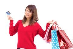 Brune tenant le cadeau et la carte de crédit Image libre de droits