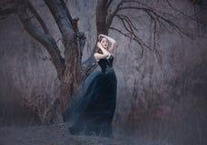 Brune tendre stupéfiante, dame dans une longue robe noire avec les bras et les épaules ouverts nus, seule la fille dans le froid  images stock