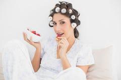 Brune étouffante dans des rouleaux de cheveux ayant un bol de fraises Photos libres de droits