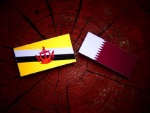 Brunei flag with Qatari flag on a tree stump isolated. Brunei flag with Qatari flag on a tree stump Royalty Free Stock Image