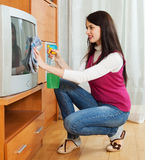 Brunentte woman cleaning TV with cleanser Royalty Free Stock Photos