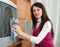 Brunentte woman cleaning TV Royalty Free Stock Image