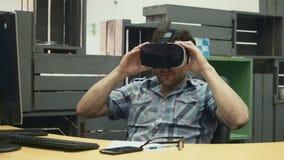 Brunet άτομο που γράφει, που χρησιμοποιεί την ταμπλέτα και που φορά vr τα γυαλιά μετά από την εργάσιμη ημέρα φιλμ μικρού μήκους