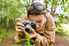 Brunet biologist in glasses photographs plants. In summer forest Stock Photos