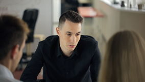 Brunet in black shirt actively discusses with colleagues strategic concepts. stock footage