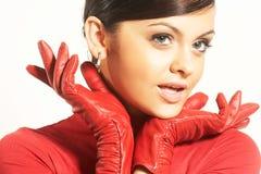 Brunet de Atractive en blusa roja y guantes rojos Fotografía de archivo