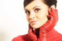 Brunet de Atractive en blusa roja y guantes rojos Imagen de archivo