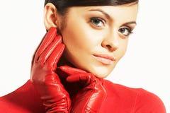 Brunet de Atractive en blusa roja y guantes rojos Fotos de archivo