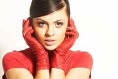 Brunet de Atractive en blusa roja y guantes rojos Foto de archivo