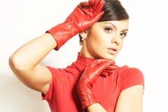 Brunet de Atractive en blusa roja y guantes rojos Foto de archivo libre de regalías