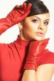 Brunet de Atractive en blusa roja y guantes rojos Fotografía de archivo libre de regalías