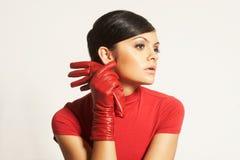 Brunet de Atractive en blusa roja y guantes rojos Imagen de archivo libre de regalías