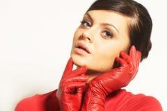 Brunet de Atractive na blusa vermelha e em luvas vermelhas Imagem de Stock Royalty Free