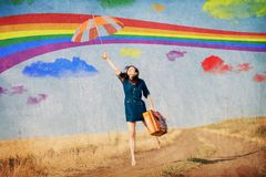 Girl fly away with umbrella and suitcase. Brunet girl fly away with umbrella and suitcase at countryside. Image made in old color style Royalty Free Stock Photos