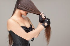 Brunet hair. Young attractive woman dressed in black corset holding her hair Stock Image