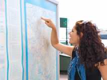 Brunet locating from map. Brunet female smiling and pointing at a map Royalty Free Stock Photos