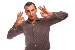 Brunet mężczyzna paskował koszulowego seansu znaka ok gest Obrazy Royalty Free