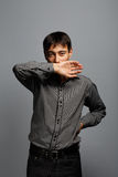 Brunet man in grey shirt with negation or covering gesture. Young asian brunet man in grey shirt standing at grey background with negation or covering gesture Stock Photo