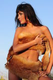 Brunet nude woman in fur. Stock Image