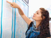 Brunet pointing at time table. Brunet female smiling and pointing at a information map Stock Photo