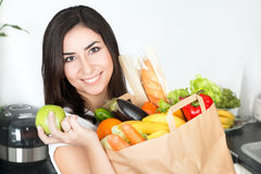 Brunet woman holding paper bag with vegetarian food. Portrait of young beautiful brunet woman standing on her kitchen with just delivered big paper bag full of Stock Photos