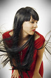 Brunet woman with long flying hair. Portrait of fresh and beautiful young brunet woman with seductive red evening dress and black hair developing on a wind. long Royalty Free Stock Photos