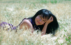 Brunet woman lying in grass Royalty Free Stock Photography