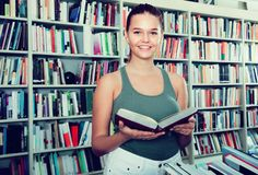 Girl chooses a book in university library. Brunete girl chooses a book in university library royalty free stock photo