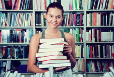 Brunete girl chooses a book in university library Royalty Free Stock Images
