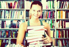 Brunete girl chose a lot of books in university library. And smiling Royalty Free Stock Photography