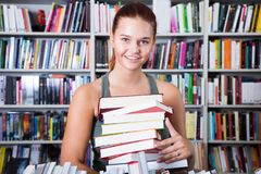 Brunete girl chose a lot of books in university library. And smiling Royalty Free Stock Photo