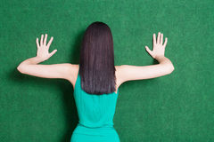 Brunete lady against green wall from back Stock Photography