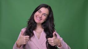 Brunetka bizneswoman gestykuluje w górę znaków pokazywać jak w kamerę na zielonym tle i szacuneku w różowej kurtce zdjęcie wideo