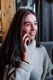 Brunetka bizneswoman opowiada na telefonie w kawiarni w pulowerze zdjęcie royalty free