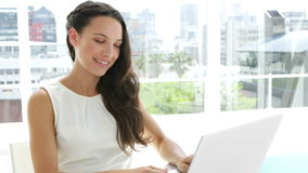 Brunetka bizneswoman pisać na maszynie na jej laptopie