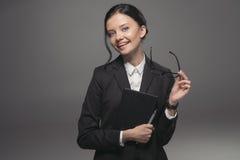 Brunetka bizneswoman w czarnym kostiumu mienia dzienniczku i ono uśmiecha się przy kamerą Zdjęcia Stock