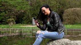 Brunetka blisko jeziora z telefonem zdjęcie wideo