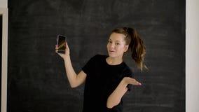 Brunetka kaukaska w sporcie trzyma smartfon w dłoni i pokazuje zajęcia zbiory wideo