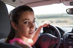 Brunetka kierowca patrzeje widza z ręką na kierownicie Obrazy Royalty Free