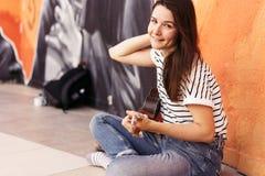 Brunetka modnisia dziewczyna siedzi ukulele i bawić się obraz royalty free
