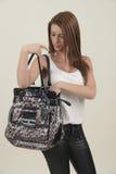 Brunetka patrzeje w jej torbie zdjęcie stock