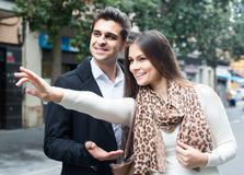 Brunetka pokazuje kierunek Indiański facet przy ulicą Zdjęcie Stock