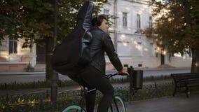 Brunetka przystojny młody człowiek w czarnych przypadkowych ubraniach, hełmofony jedzie rower miasto parkiem z gitarą w czarnej s zdjęcie wideo