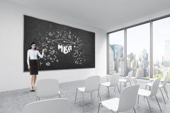 Brunetka robi prezentaci w sala lekcyjnej w nowożytnym fantazi biurze lub uniwersytecie Biali krzesła, czarny chalkboard na wal Zdjęcie Stock