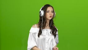 Brunetka słucha przez hełmofonów z energiczny muzycznym i buduje grymasy zielony ekran zdjęcie wideo