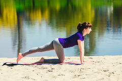 Brunetka w błękitnej sport koszula na sprawności fizycznej matowy robić ćwiczy na plaży Kobieta robi sprawności fizycznej ćwiczen Fotografia Stock